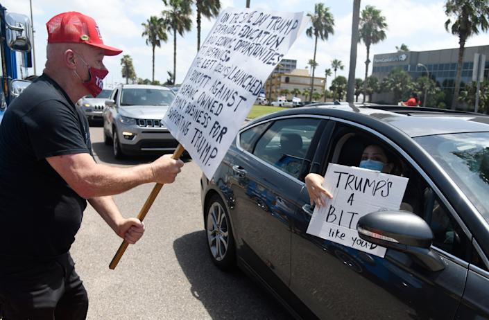 Counter protesters drive by Trump supporters at the Selena statue, Saturday, July 11, 2020. Cars drove down Shoreline Drive.