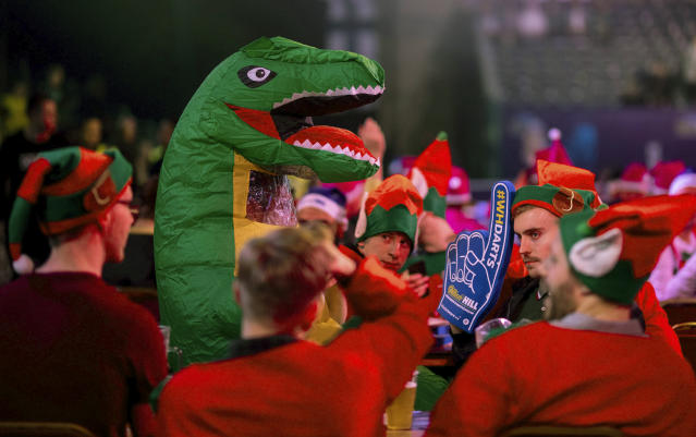A fan sits in fancy dress during day nine of the of the darts World Championship at Alexandra Palace, London, Saturday Dec. 21, 2019. (Steven Paston/PA via AP)