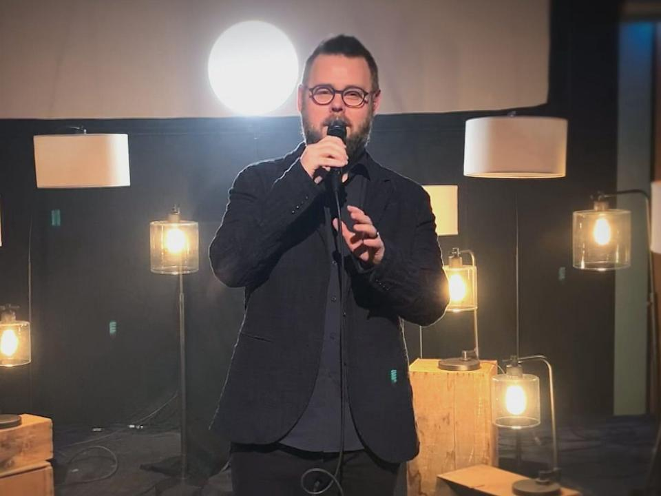"""Todd Tilghman singing on video for """"The Voice"""" in a room with several lights"""