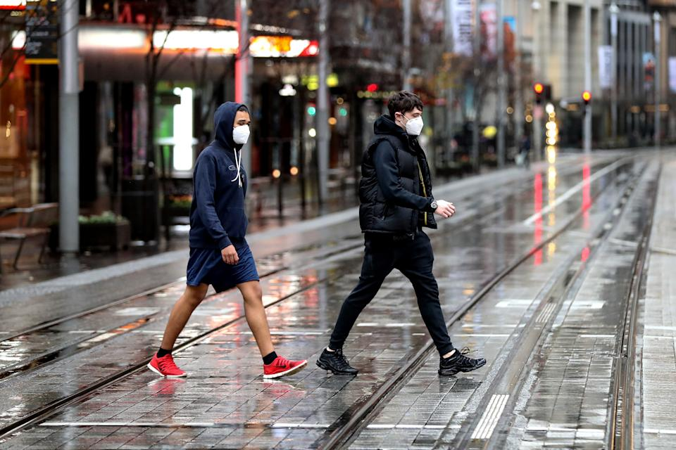 Pedestrians wearing protective masks walk across a road during a lockdown.