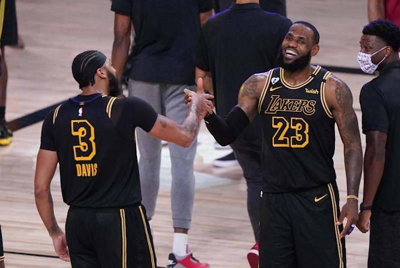 Los Angeles Lakers' LeBron James (23) celebrates with teammate Anthony Davis (3) after an NBA conference final playoff basketball game against the Denver Nuggets Sunday, Sept. 20, 2020, in Lake Buena Vista, Fla. The Lakers won 105-103. (AP Photo/Mark J. Terrill)