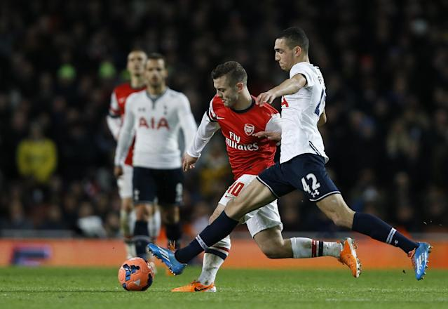 Arsenal's Jack Wilshere, centre, struggles to control the ball as Tottenham's Nabil Bentaleb, right, comes in to challenge during the English FA Cup third round soccer match between Arsenal and Tottenham Hotspur at the Emirates Stadium in London, Saturday, Jan. 4, 2014. (AP Photo/Kirsty Wigglesworth)