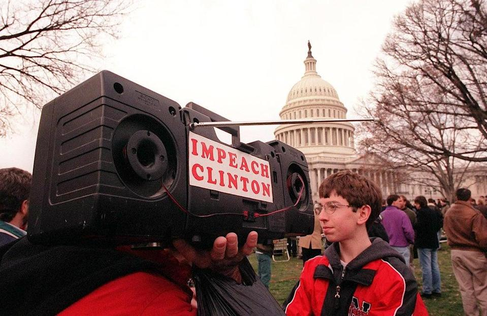 A man shoulders a portable radio with the words 'Impeach Clinton' pasted on its side as the US House of Representatives votes on the articles of impeachment against US president Bill Clinton on 19 December 1998 at the Capitol (MARIO TAMA/AFP via Getty Images)
