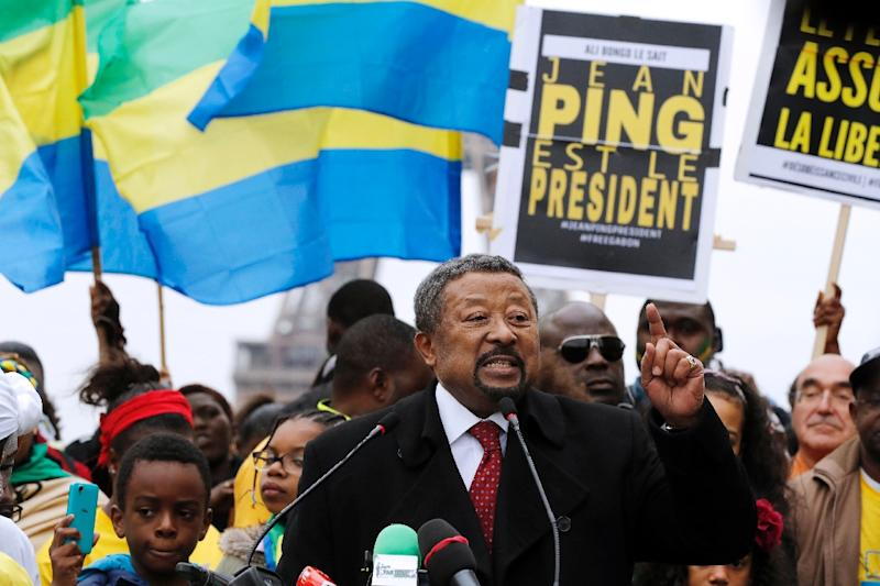 Gabonese opposition leader Jean Ping (C), surrounded by supporters waving Gabonese flags, gestures as he speaks  on the Human Rights Esplanade