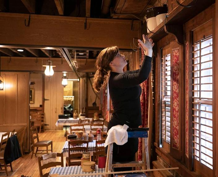 Angus Barn employee Rebecca Layton arranges an antique display in one of the dining rooms on Tuesday, May 19, 2020 in Raleigh, N.C. Owner Van Eure is preparing to open her dining rooms in anticipation of Gov. Roy Cooper lifting his coronavirus restrictions.