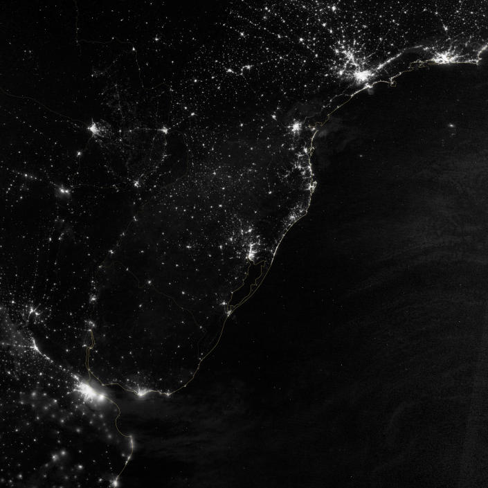 """This image of part of the Atlantic coast of South America was acquired by the Suomi NPP satellite on the night of July 20, 2012. The image was made possible by the """"day-night band"""" of the Visible Infrared Imaging Radiometer Suite (VIIRS), which detects light in a range of wavelengths from green to near-infrared and uses filtering techniques to observe dim signals such as city lights, gas flares, auroras, wildfires, and reflected moonlight. (NASA)"""