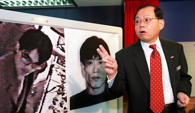Andy Tsang, Chief Superintendent of the Organsied Crime and Triad Bureau, shows the photos of an unidentified member of a gang led by Kwai Ping-hung (right) wanted in connection with the shooting of two police officers in Mong Kok in May 2001. Photo: SCMP