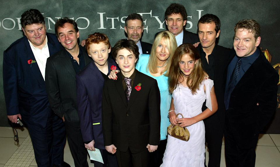 """Cast including British actors Robbie Coltrane (L), Rupert Grint (3rd L), Daniel Radcliffe (4th L), Hermione Grainger (3rd R) and Kenneth Branagh (R), pose with director Chris Columbus (2nd L) and unidentified others at London's Odeon Leicester Square for the world premiere of """"Harry Potter and the Chamber of Secrets"""" on November 3, 2002. The film, which is due to go on official release on November 15, 2002,  is the second screen adaptation from the series of Harry Potter books by British author [J K Rowling.]"""
