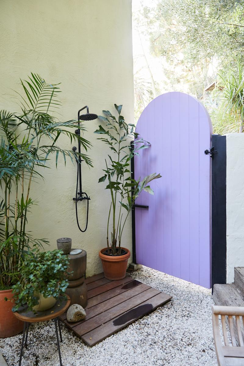 """""""One of the nice things about Los Angeles is the weather allows you to shower outside,"""" says Bennett about this secluded corner of the garden, tucked behind an arched door whose purple color was inspired by the work of Mexican architect Luis Barragán."""
