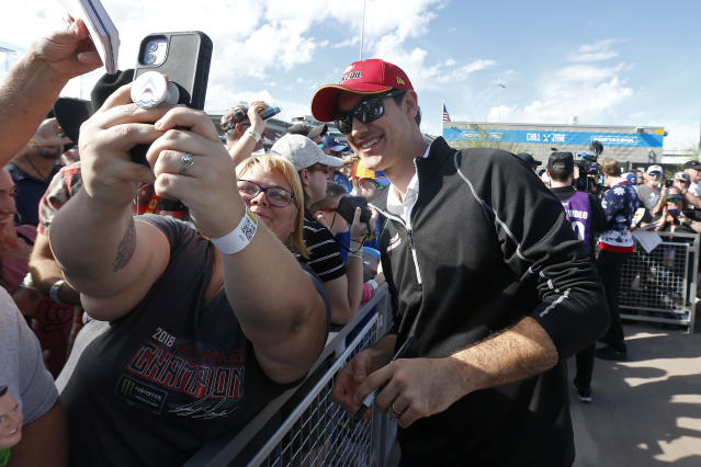 Driver Joey Logano, right, stops to take a photo with a fan prior to ae NASCAR Cup Series auto race at ISM Raceway, Sunday, Nov. 10, 2019, in Avondale, Ariz. (AP Photo/Ralph Freso)