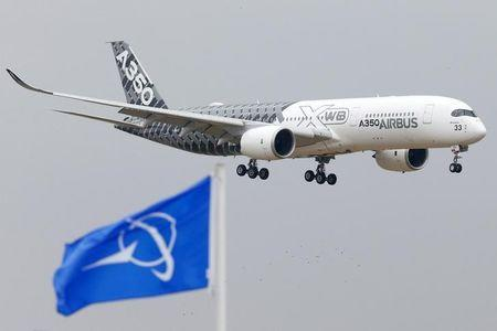An Airbus A350 jetliner flies over Boeing flags as it lands after a flying display during the 51st Paris Air Show at Le Bourget airport near Paris, June 15, 2015. REUTERS/Pascal Rossignol/Files