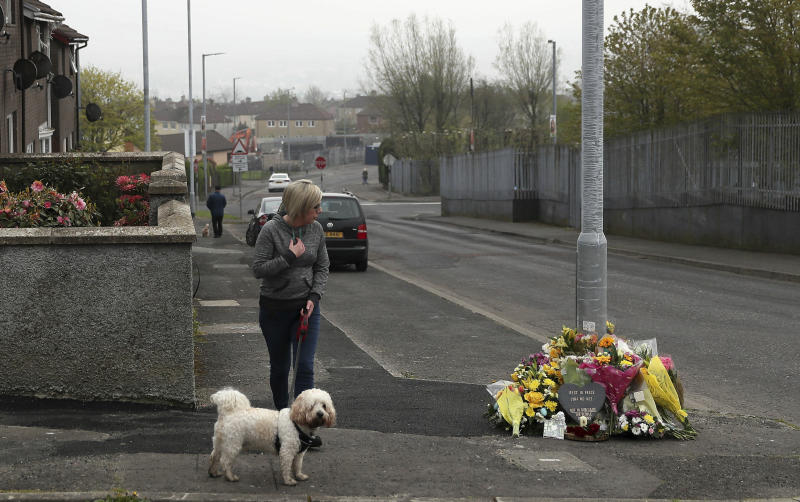 A woman reacts as she stops to pay her respects at the scene Saturday April 20, 2019, in Londonderry, Northern Ireland, where 29-year old journalist Lyra McKee was fatally shot. Police in Northern Ireland on Saturday arrested two teenagers in connection with the fatal shooting of investigative journalist Lyra McKee was shot and killed during rioting Thursday night. (Brian Lawless/PA via AP)