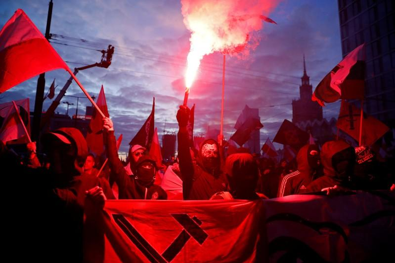 People carry Polish flags and flares during a march marking the 101st anniversary of Polish independence in Warsaw