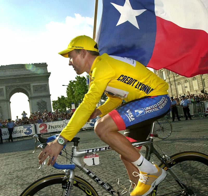 FILE - This July 29, 2001 file photo shows Lance Armstrong riding past the Arc de Triomphe waving the Texas flag after he won the Tour de France cycling race, in Paris. The superstar cyclist, whose stirring victories after his comeback from cancer helped him transcend sports, chose not to pursue arbitration in the drug case brought against him by the U.S. Anti-Doping Agency. That was his last option in his bitter fight with USADA and his decision set the stage for the titles to be stripped and his name to be all but wiped from the record books of the sport he once ruled.  (AP Photo/Christophe Ena, File)