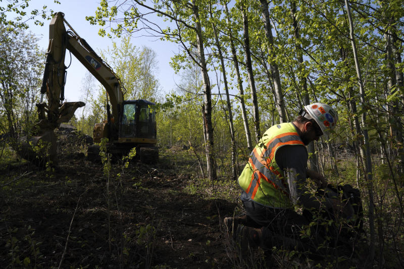 In this Wednesday, May 29, 2019, Eric Olson, right, gathers his tools as contractor Robert Radotich uses a backhoe to dig areas so the soil stratification can be observed which will help them engineer and design the infiltration pods for the Polymet copper-nickel mine in Hoyt Lakes, Minn. The developers of the proposed mine in northern Minnesota are courting bankers for nearly $1 billion to move ahead with the project, even as opponents hold out hope of blocking the operation due to fears of water pollution.  (Anthony Souffle/Star Tribune via AP)