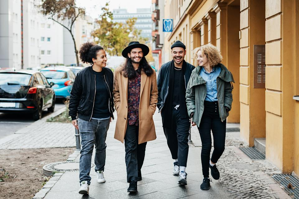 A stylish group of friends on chatting while making their way to a bar together for some drinks.