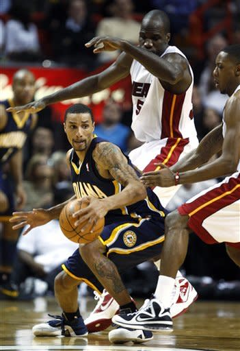Indiana Pacers guard George Hill, left, looks for an opening past Miami Heat center Joel Anthony, rear, and guard Mario Chalmers, right, during the first half of an NBA basketball game, Wednesday, Jan. 4, 2012, in Miami. (AP Photo/Wilfredo Lee)