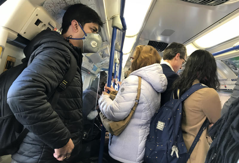 A traveller wears a mask on a busy tube in London, Monday, March 16, 2020. For most people, the new coronavirus causes only mild or moderate symptoms, such as fever and cough. For some, especially older adults and people with existing health problems, it can cause more severe illness, including pneumonia. (AP Photo/Kirsty Wigglesworth)