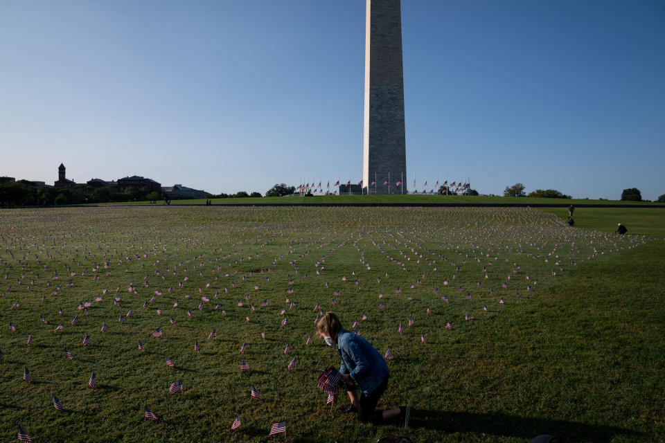 Carmen Wilke, a volunteer with the COVID Memorial Project, places flags representing American lives lost to the coronavirus at the Washington Monument in Washington, Sept. 22, 2020. (Anna Moneymaker/The New York Times)