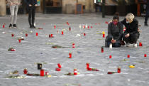 People pay their respects to victims of the COVID-19 pandemic at a spontaneous memorial at the Old Town Square in Prague, Czech Republic, Monday, March 29, 2021. The coronavirus pandemic is unleashing enormous suffering as infection rates rise across central Europe even as the Czech Republic and Slovakia, recently among the worst-hit areas in the world, are finally seeing some improvements following tight lockdowns. (AP Photo/Petr David Josek)