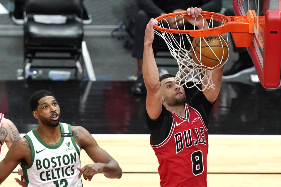 Chicago Bulls guard Zach LaVine, right, dunks past Boston Celtics center Tristan Thompson during the second half of an NBA basketball game in Chicago, Friday, May 7, 2021. (AP Photo/Nam Y. Huh)