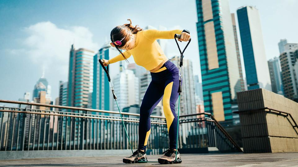 Young Asian sports woman exercising with a resistance band outdoors, with urban city skyline as background.