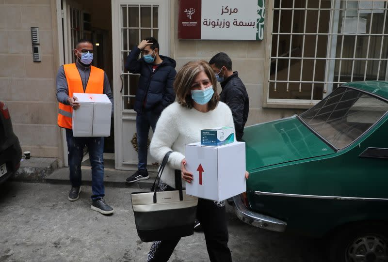 A woman carries a box of donations distributed by Basmeh we Zeitooneh, an aid organisation, in Bourj Hammoud