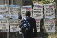 A man reads newspaper headlines on a street of Harare, Sunday, Nov. 8, 2020. Zimbabwean President Emmerson Mnangagawa has sent a congratulatory message to U.S. President-elect Joe Biden who won the U.S. presidential election, beating incumbent Donald Trump. (AP Photo/Tsvangirayi Mukwazhi)