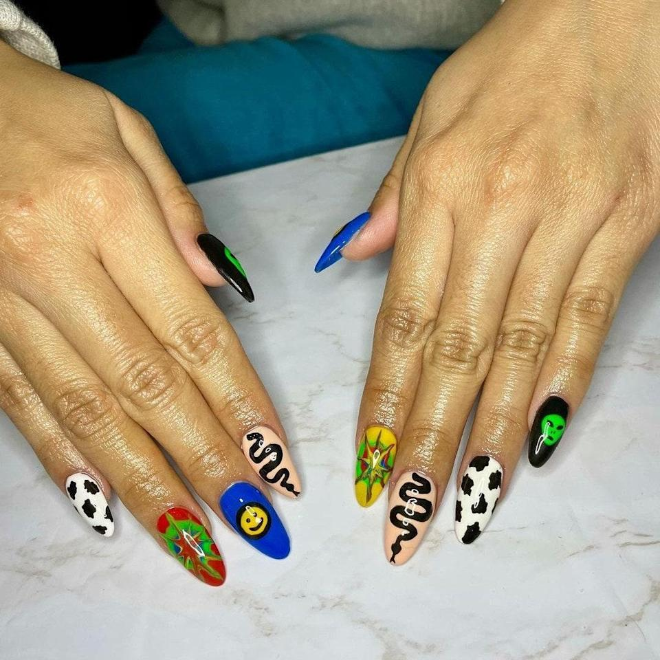 """Bay Area-based nail artist <a href=""""https://www.instagram.com/downfortheclaws/"""" rel=""""nofollow noopener"""" target=""""_blank"""" data-ylk=""""slk:Agatha Mae"""" class=""""link rapid-noclick-resp"""">Agatha Mae</a> hand-painted each individual design (five in total) onto these almond-shaped nails. One nail has a black base with a slim, green alien drawn on top. On the next finger is a cow print with a white base and black spots. There's another animal featured in this mani — a slithering snake drawn in black polish on a peach nail. There's also a bright yellow smiley face on a cobalt nail, and, for the last design, she used different colors on both nails. One finger has a red base with green, blue, and a darker red polish spread out on the nail; the other hand has a yellow nail with green, red, and blue colors instead."""