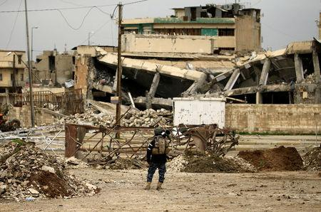 A federal policeman carries his weapon as he stands near buildings destroyed in clashes during a battle against Islamic State militants, in Mosul