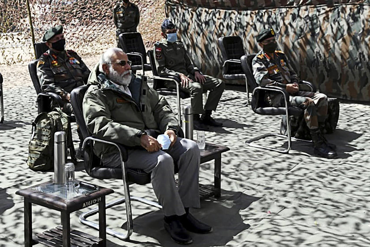 India's Prime Minister Narendra Modi (L) sits during a briefing with military commanders as he arrives in Leh, the joint capital of the union territory of Ladakh. (Photo by Handout / PIB / AFP)