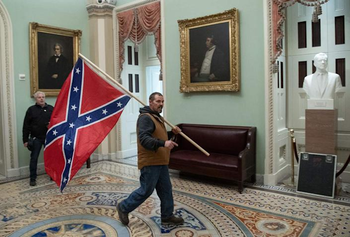 A man bearing a Confederate battle flag walks in front of a portrait of former Vice President John C. Calhoun.