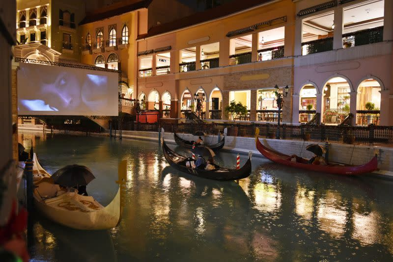 People on gondolas watch a movie while observing social distancing amid coronavirus disease (COVID-19) at a float-in cinema, in Venice Grand Canal Mall, Taguig City, Metro Manila