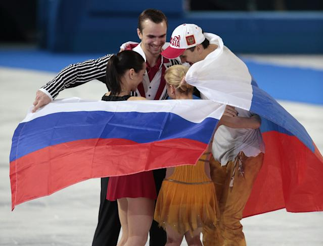 Tatiana Volosozhar and Maxim Trankov of Russia and Ksenia Stolbova and Fedor Klimov of Russia celebrate after they placed first and second following the flower ceremony for the pairs free skate figure skating competition at the Iceberg Skating Palace during the 2014 Winter Olympics, Wednesday, Feb. 12, 2014, in Sochi, Russia. (AP Photo/Ivan Sekretarev)