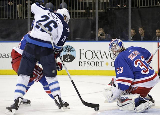 Winnipeg Jets right wing Blake Wheeler (26) maneuvers the puck in front of New York Rangers goalie Cam Talbot (33) as he gets tangled up with New York Rangers defenseman Anton Stralman in the first period of their NHL hockey game in New York, Monday, Dec. 2, 2013. (AP Photo/Kathy Willens)