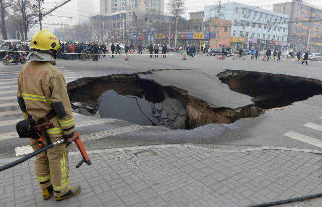 A firefighter stands next to a cave-in at a crossroad in Taiyuan, Shanxi province, December 26, 2012. The cause of the cave-in, measuring about 6 meters (20 ft.) in depth, 10 meters (32.8 ft.) in diameter, is still under investigation. Three coal gas tubes and one water tube were broken during the collapse and firefighters are trying to dilute the coal gas at the site, reported local media. REUTERS/Stringer (CHINA - Tags: DISASTER SOCIETY) CHINA OUT. NO COMMERCIAL OR EDITORIAL SALES IN CHINA - RTR3BWN5