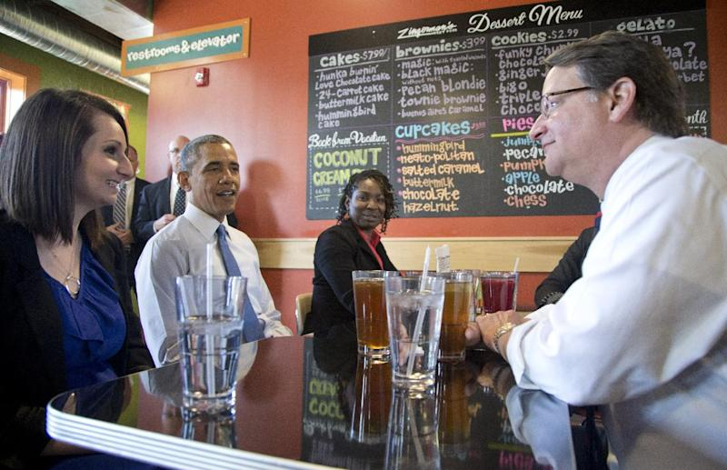President Barack Obama sitting between Mira Friedlander, a 22 year old senior at the University of Michigan, left, and Aisha Turner, 36, a mother of three who has worked for nearly two decades as a server, and Rep. Gary Peters, D-Mich., right, have lunch at Zingerman's Deli in Ann Arbor, Mich., Wednesday, April 2, 2014, before the president was to speak at the University of Michigan about his proposal to raise the national minimum wage. (AP Photo/Carolyn Kaster)