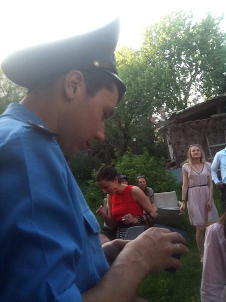 In this Saturday, May 18, 2013 photo taken by an actress of the Free Theater Marina Yurevich with a mobile phone, a policeman checks ID of actors and spectators before a performance of the Free Theater in Minsk, Belarus. Two emotions course through the audience at the Belarus Free Theater _ excitement at seeing an innovative production and fear that police will haul them away. The theater, in a cramped and tumbledown house in the capital, Minsk, is a rare crucible of dissent and experimentation in quasi-Soviet Belarus, taking on topics such as political dissent and homosexuality. (AP Photo/Sergei Grits)