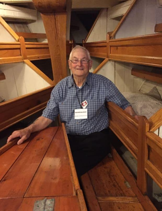 Maurice Kearley, 93, the only doryman still alive who sailed on the L.A. Dunton, has travelled to Mystic three times to see it. Here he has his arm in the bunk where he slept when he fished on it in 1953.
