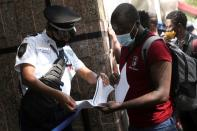 An employee checks the documents of a migrant from Haiti as he lines up to regularise his migratory situation outside of the Mexican Commission for Aid to Refugees (COMAR), in Mexico City