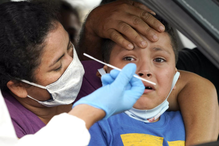 Lillian Palacios, left, holds her son, Daniel, 7, as a healthcare professional prepares to take a sample from him at a United Memorial Medical Center COVID-19 testing site Friday, June 26, 2020, in Houston. (David J. Phillip/AP)
