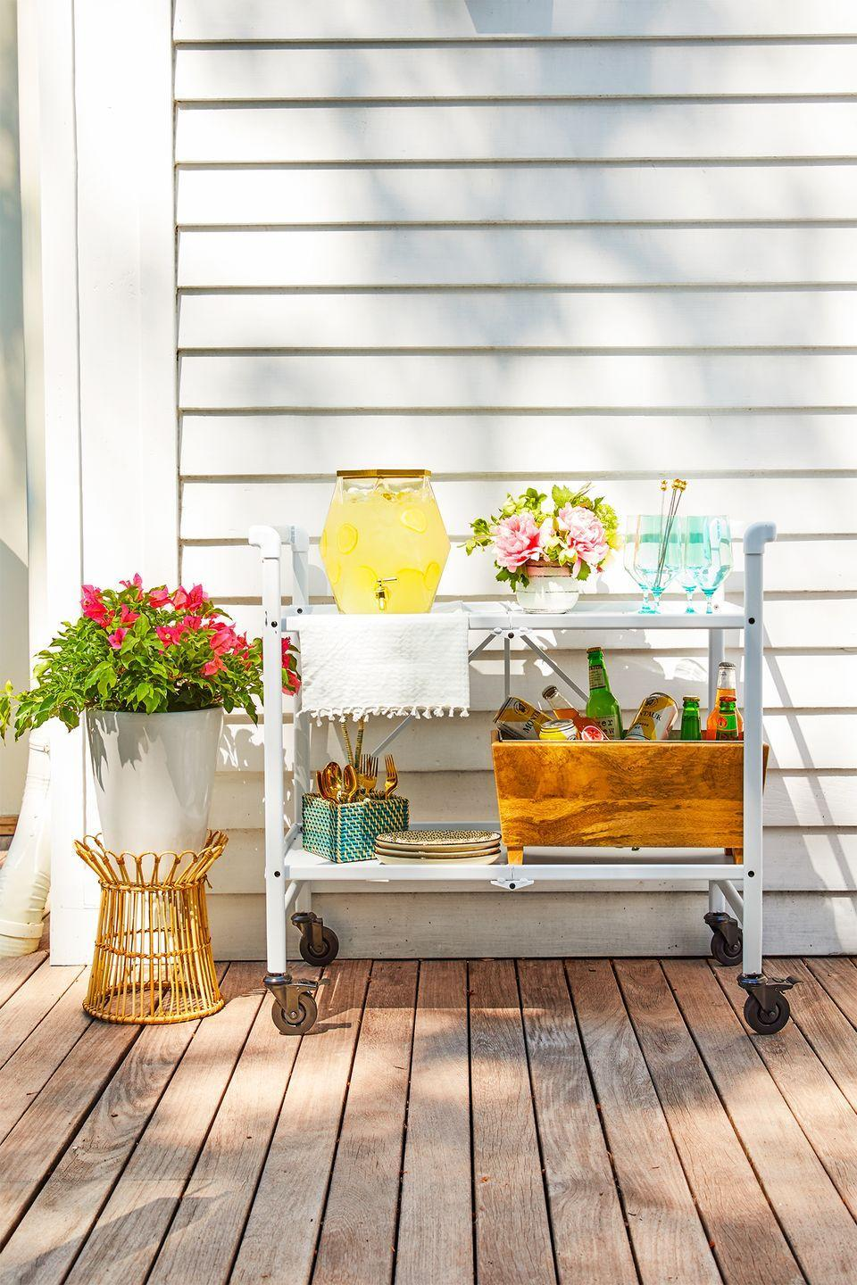 """<p>When done right, utility carts become the ultimate drink station. Deck out the shelves with coolers, glasses, utensils, and pitchers full of party punch (or another drink of your choice). </p><p><strong>RELATED:</strong> <a href=""""https://www.goodhousekeeping.com/home/g31206630/outdoor-bar-ideas/"""" rel=""""nofollow noopener"""" target=""""_blank"""" data-ylk=""""slk:The Best Outdoor Bar Carts"""" class=""""link rapid-noclick-resp"""">The Best Outdoor Bar Carts </a></p>"""