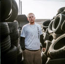 """In this photo made with a medium format film camera, Steven Ash, 33, stands for a portrait while working at the tire shop his family owns and where he overdosed just days before in Huntington, W.Va., Wednesday, March 17, 2021. Ash was 19 when he took his first OxyContin pill and his life unraveled after that, cycling through jails, he said. The last year has been particularly brutal. His cousin died from an overdose in somebody's backyard. He has a friend in the hospital in her 20s scheduled for open-heart surgery from shooting drugs with dirty needles, and the doctors aren't sure she'll make it. He had three agonizing surgeries himself from drug-related infections. He took more drugs to numb the pain, but it made things worse, a vicious cycle, he said. He knows he's putting his mother through hell. """"I fight with myself every day. It's like I've got two devils on one shoulder and an angel on the other,"""" he said. """"Who is going to win today?"""" (AP Photo/David Goldman)"""