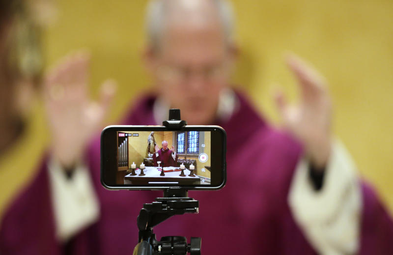 In Seattle, a cell phone is used to live stream a Catholic mass at St. James Cathedral amid the coronavirus outbreak. (AP Photo/Elaine Thompson)