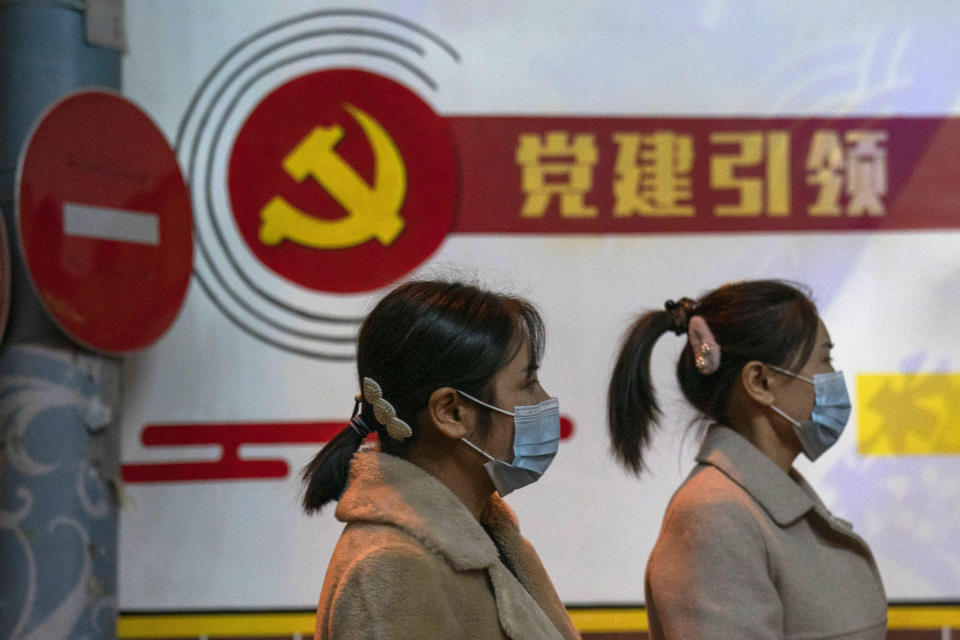 "Residents wearing masks pass by the Communist party logo and the slogan ""Party building leadership"" in Beijing on Thursday, Oct. 29, 2020. China will promote ""technological self-reliance"" under the ruling Communist Party's latest five-year plan but will open further to trade, officials said Friday. (AP Photo/Ng Han Guan)"