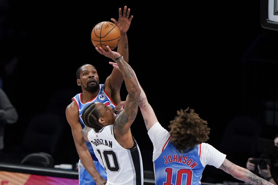 Brooklyn Nets' Kevin Durant, left, and Tyler Johnson, right, defend San Antonio Spurs' DeMar DeRozan, center, during the second half of an NBA basketball game Wednesday, May 12, 2021, in New York. (AP Photo/Frank Franklin II)