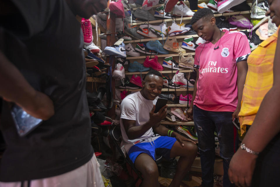 Jhon Celestin, deported from the United States two days earlier, talks with a friend in Chile while shopping for sneakers in Port-au-Prince, Haiti, Friday, Sept. 24, 2021. Celestin's new plan is to return to Chile, where he built homes as a construction worker after obtaining a visa. (AP Photo/Joseph Odelyn)
