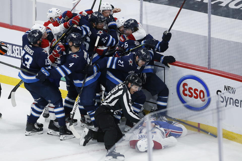 Montreal Canadiens' Jake Evans (71) is protected as he lies motionless on the ice after getting hit by Winnipeg Jets' Mark Scheifele (55) during the third period of Game 1 of an NHL hockey Stanley Cup second-round playoff series Wednesday, June 2, 2021, in Winnipeg, Manitoba. (John Woods/The Canadian Press via AP)