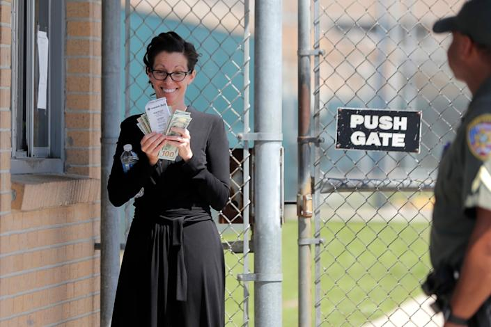 Shaye Spell, wife of pastor Tony Spell, flashes wads of cash as she waits outside the East Baton Rouge parish jail. Tony Spell was arrested for flouting lockdown orders during the coronavirus pandemic: AP