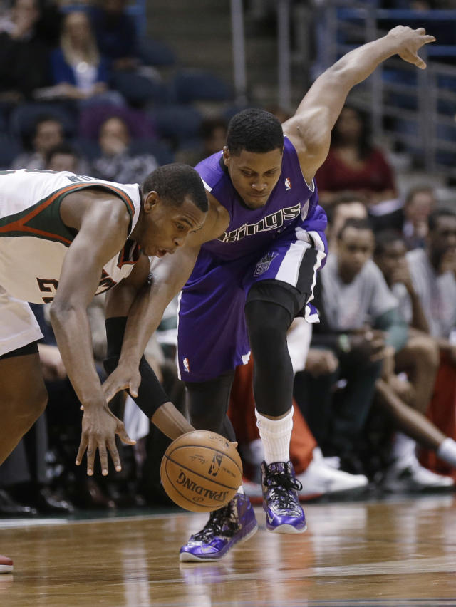 Sacramento Kings' Rudy Gay, right, and Milwaukee Bucks' Khris Middleton reach for a loose ball during the second half of an NBA basketball game Wednesday, March 5, 2014, in Milwaukee. (AP Photo/Jeffrey Phelps)